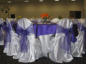 White Chair Covers with a Purple Lace Bow Tied Around Them
